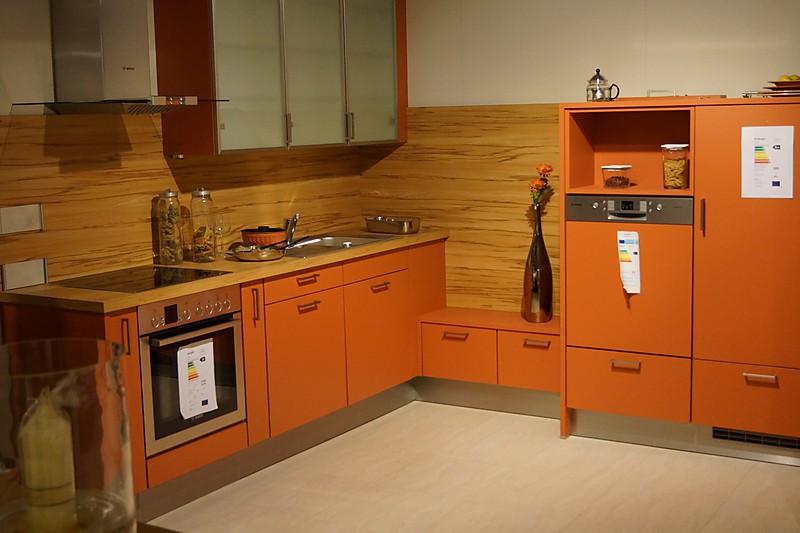 Ausstellungsküche in Korallenrot mit Elektrogeräten. Backofen, Geschirrspüler und Dunstabzugshaube.