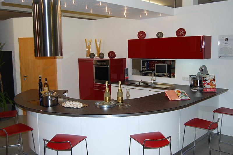 Weiß, rote Ausstellungsküche mit runder Arbeitsplatte. Arbeitsplatte dient auch als Theke für Besucher. Mit Induktionskochfeld, Backofen, Geschirrspüler, Dunstabzugshaube und Kühlschrank.
