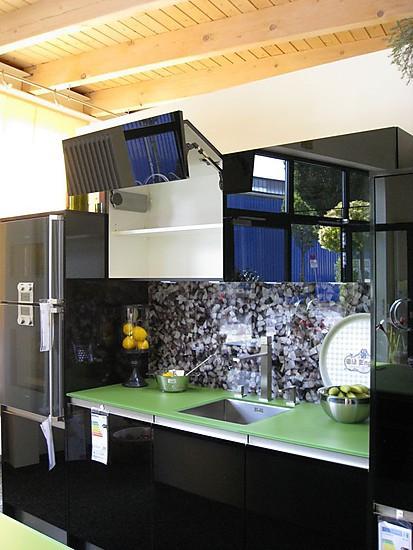 Schwarze Design Ausstellungskueche mit Oberschraenken und gemusterter Glasrückwand