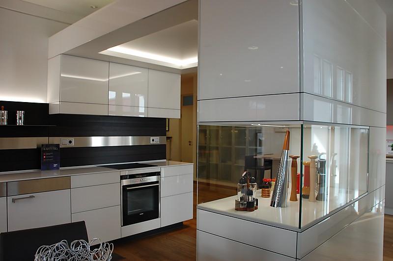 Moderne Ausstellungsküche mit weißen Glafronten und Glasvitrine im Hochschrank